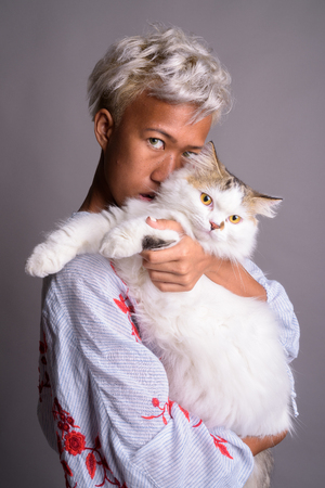 Young beautiful woman with short hair holding Persian cat 写真素材