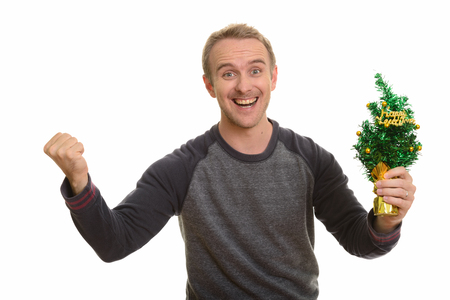 Happy Caucasian man holding Happy New Year tree looking excited