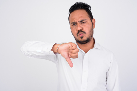 Studio shot of stressed bearded Indian businessman getting bad news Фото со стока