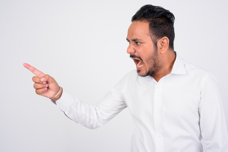 Studio shot of angry bearded Indian businessman shouting and pointing finger