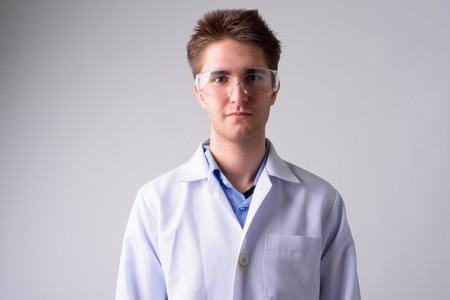 Young handsome man doctor with protective glasses