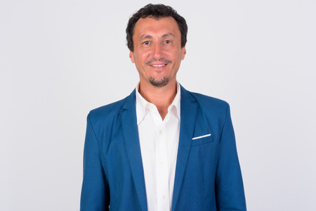 Portrait of happy mature businessman smiling against white background