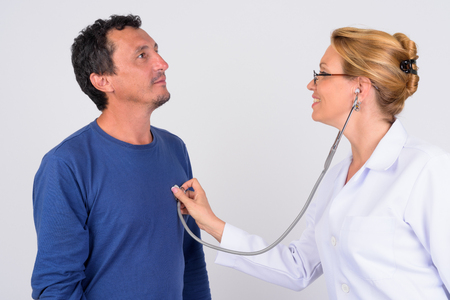 Mature woman doctor checking mature man patient against white background