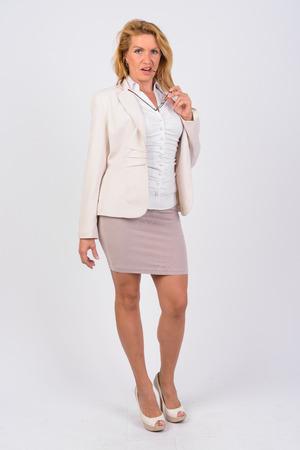 Retrato, de, maduro, mujer de negocios, morder, anteojos, contra, fondo blanco