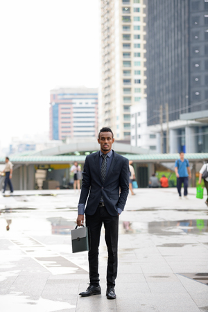 Young African businessman carrying briefcase in the city outdoors