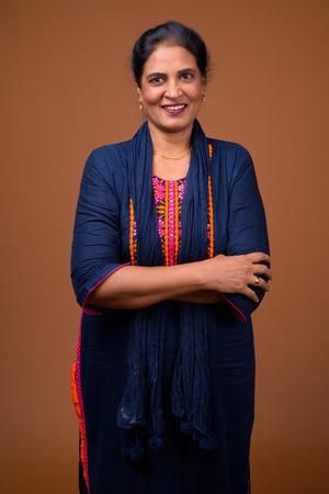 Szczęśliwa dojrzała indyjska kobieta uśmiechająca się na brązowym tle