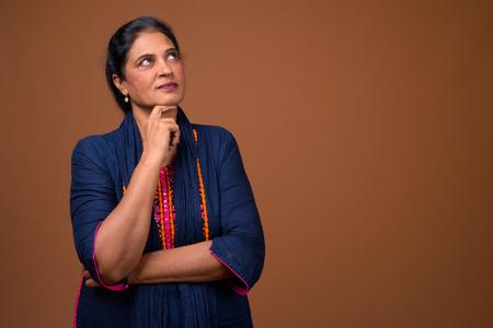 Portrait of mature beautiful Indian woman thinking
