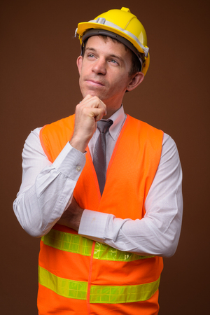 Portrait of man construction worker against brown background Stock Photo
