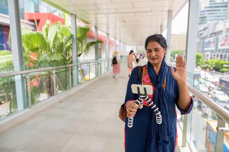 Mature beautiful Indian woman vlogging using mobile phone