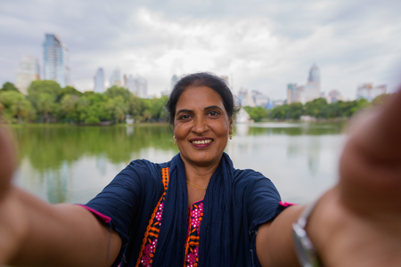 Personal point view of happy mature Indian woman taking selfie 写真素材 - 115477660