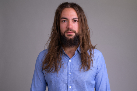 Portrait of young handsome bearded businessman with long hair Reklamní fotografie