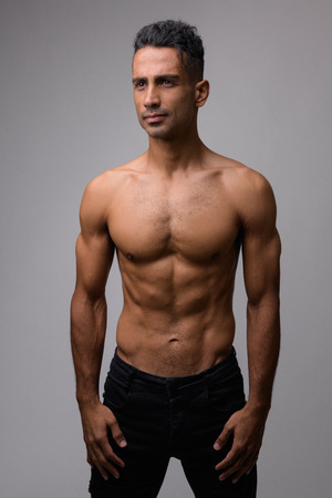 Portrait of young muscular Persian man thinking shirtless