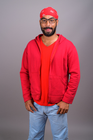 Portrait of young handsome Indian man wearing red shirt