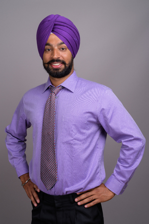 Young handsome Indian Sikh businessman wearing turban against gr