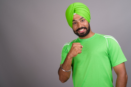 Young handsome Indian Sikh man wearing turban and green shirt Stock Photo