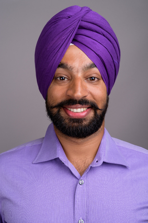 Face of Indian Sikh businessman wearing turban and smiling