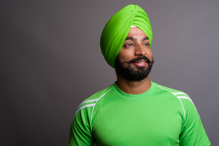 Young handsome Indian Sikh man wearing turban and green shirt Foto de archivo