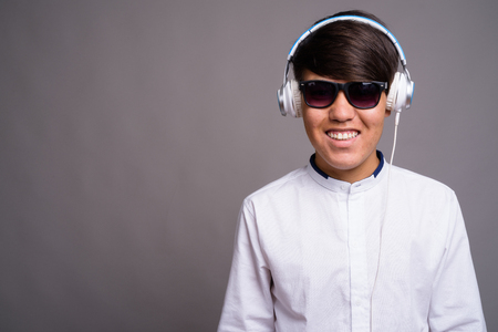 Young Asian teenage boy listening to music against gray backgrou 版權商用圖片