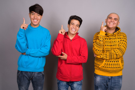 Three young Asian men wearing warm clothing against gray backgro Stock Photo