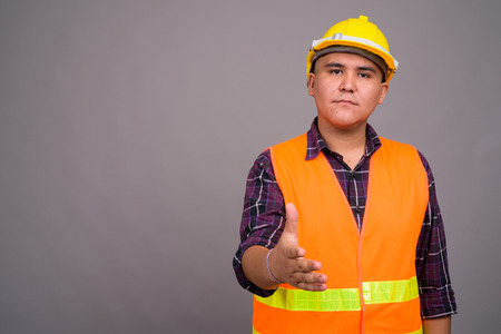 Young Asian man construction worker against gray background