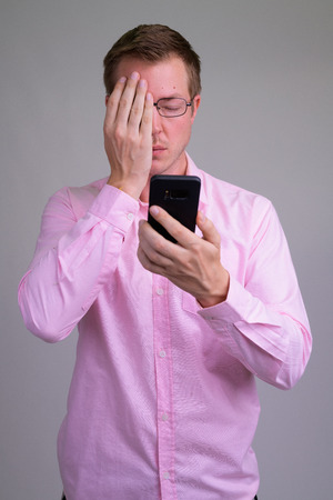Young stressed businessman using phone and covering face Stockfoto