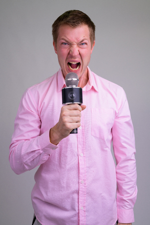 Angry young businessman as host shouting on the microphone