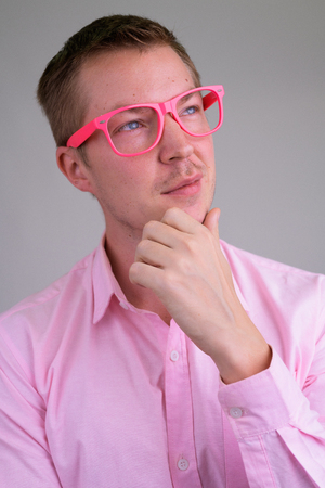 Face of young handsome businessman thinking with pink eyeglasses