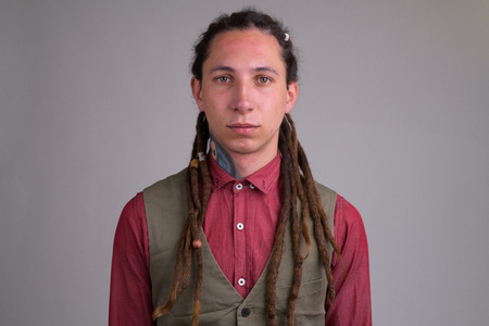 Face of young handsome businessman with dreadlocks Foto de archivo