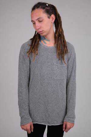Portrait of sad young man with dreadlocks thinking and looking down
