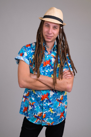 Portrait of happy young tourist man with dreadlocks crossing arms