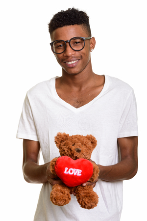 Young happy African man holding teddy bear with love and heart s