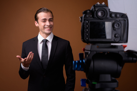 Young happy Caucasian businessman influencer vlogging in studio