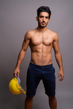 Joven guapo persa trabajador de la construcción sin camisa contra Foto de archivo