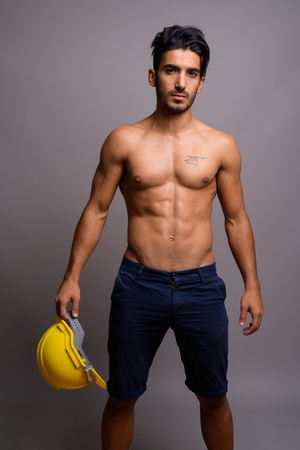 Young handsome Persian man construction worker shirtless against
