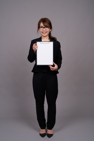 Full length portrait of young Asian businesswoman standing