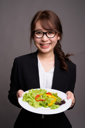 Happy Asian businesswoman holding salad while smiling Banque d'images