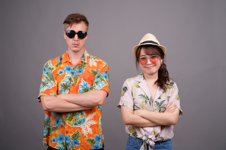 Multi ethnic tourist couple wearing sunglasses and Hawaiian shirt