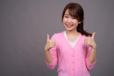 Young beautiful Asian woman wearing pink shirt 스톡 콘텐츠