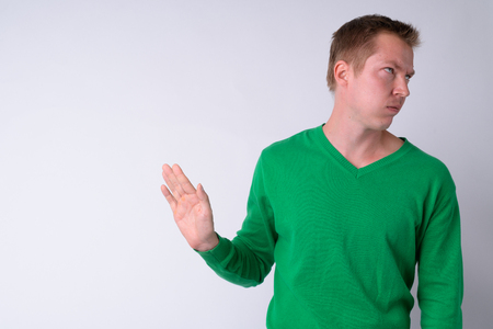 Portrait of annoyed young man showing stop gesture