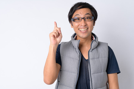 Portrait of happy Japanese man pointing up ready for hiking