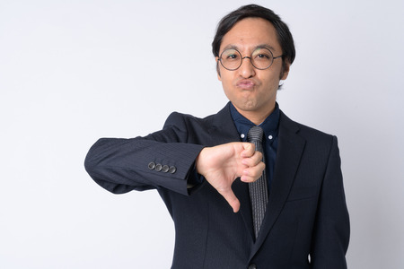 Portrait of Japanese businessman in suit giving thumbs down