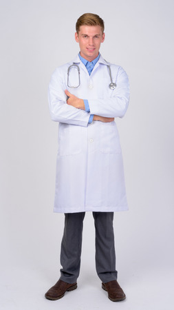 Full body shot of young happy man doctor smiling with arms crossed