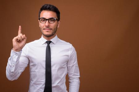 Joven empresario hispano guapo contra el fondo marrón