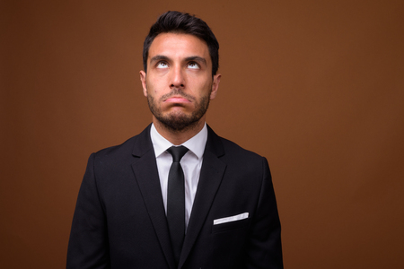 Young handsome Hispanic businessman against brown background Фото со стока