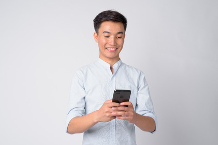 Portrait of young happy Asian businessman using phone Stock Photo