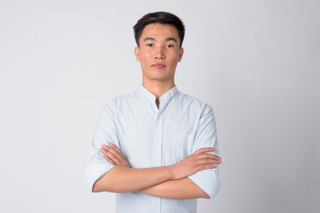 Portrait of young handsome Asian businessman with arms crossed Standard-Bild