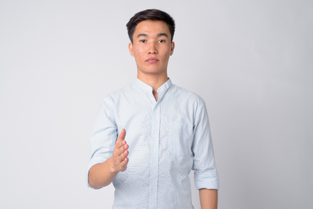Portrait of young handsome Asian businessman giving handshake