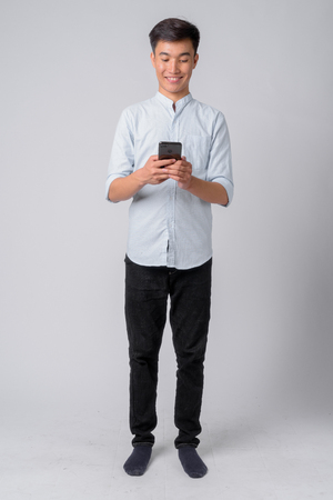 Full body shot of young happy Asian businessman using phone Standard-Bild