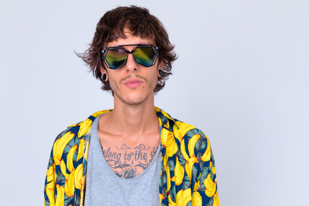 Face of young rebellious man wearing sunglasses looking cool