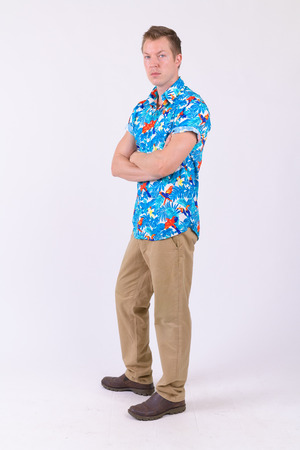 Full body shot of young handsome tourist man with arms crossed